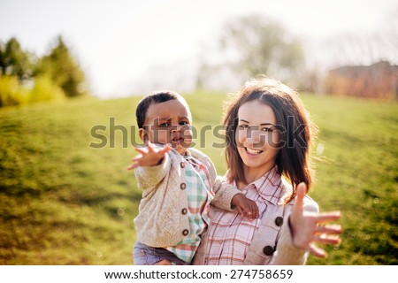 Interracial family. Caucasian mother and her african american son having fun in park - stock photo