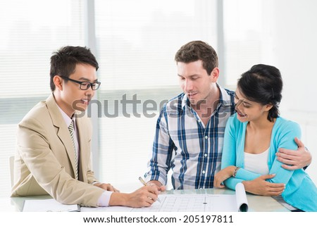 Interracial family having consultation with a real estate agent - stock photo