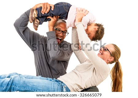 Interracial family is having fun. Adoption is a success. Active family celebrating first birthday of a mulatto child. Mixed marriages concept. - stock photo