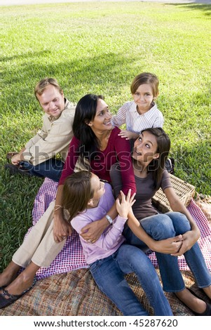 Interracial family with three children having picnic in park - stock photo
