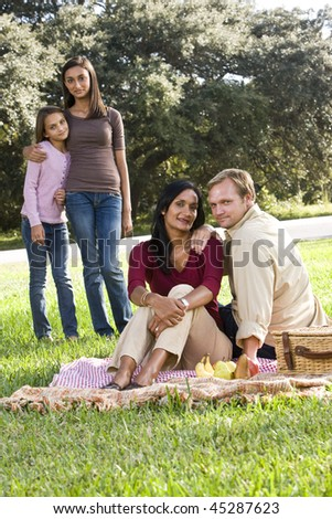 Interracial family with two children having picnic on sunny day in park - stock photo