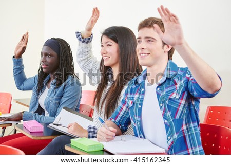 Interracial group of students raising their hands in class