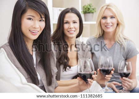 Interracial group of three beautiful young women friends at home drinking red wine together - stock photo