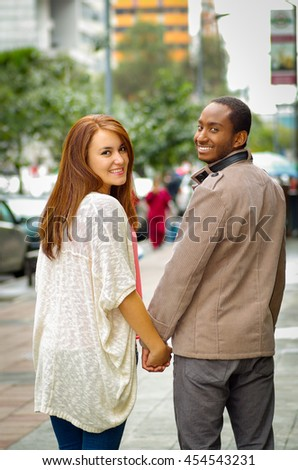 Interracial happy charming couple wearing casual clothes walking holding hands, turns around heads for camera in outdoors urban environment - stock photo