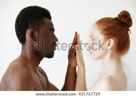 Interracial multi-ethnic couple. Intimate portrait of African male and pretty Caucasian female with red hair and freckles looking at each other with loving and passionate expression, holding hands - stock photo