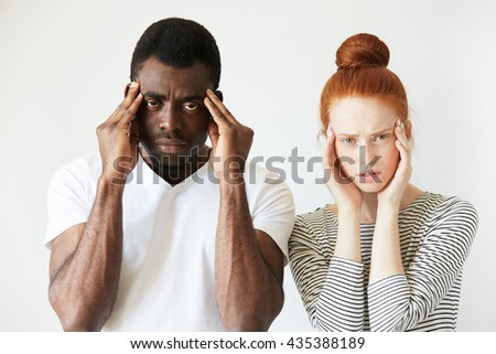 Interracial relationships concept. Black man in white polo shirt and his Caucasian redhead wife, having headache, holding hands on their temples, looking at the camera, exhausted with endless quarrels - stock photo