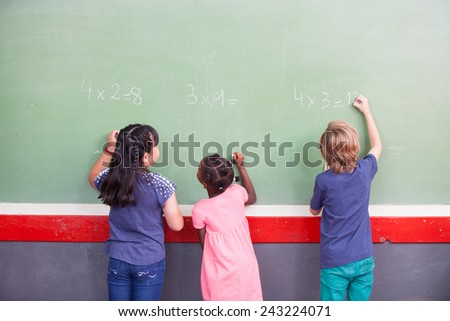 Interracial students writing numbers on chalkboard at elementary school. - stock photo
