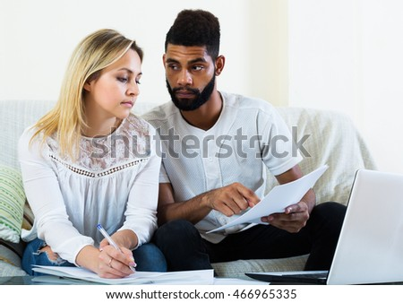 Interracial unhappy young family filling papers for mortgage indoors