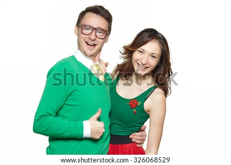 Interracial weird nerd couple showing OK sign. Caucasian young man wearing eyeglasses and smiling asian woman showing thumbs up sign and wearing 50 style clothes. Fifties nerd concept - stock photo