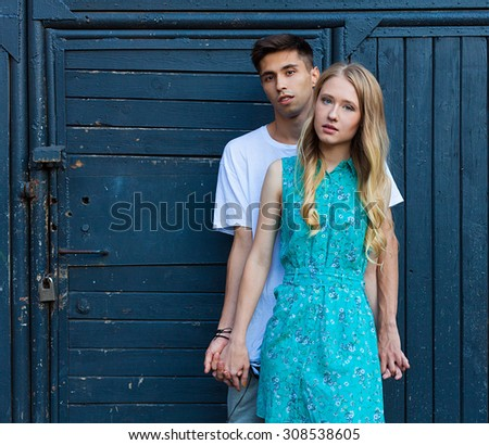 Interracial young couple in love outdoor. Stunning sensual outdoor portrait of young stylish fashion couple posing in summer. Girl looking at the camera. Hispanic man, Caucasian girl - stock photo
