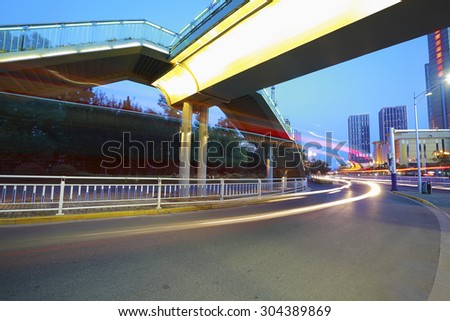 Intersection of urban footbridge and highway auto with light trails of night scene - stock photo