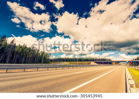 Intersections suburban highway. View from the road level, image in the yellow-blue toning - stock photo