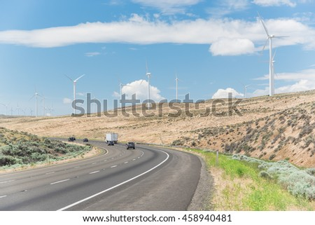 Interstate Highway I90 and row of wind turbines of windfarm in Ellensburg, Washington, US. Windmills again blue cloud sky. Clean, sustainable, renewable energy. Transportation, electricity background.