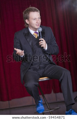 interview with male actor on the stage - spotlight on right top corner - stock photo