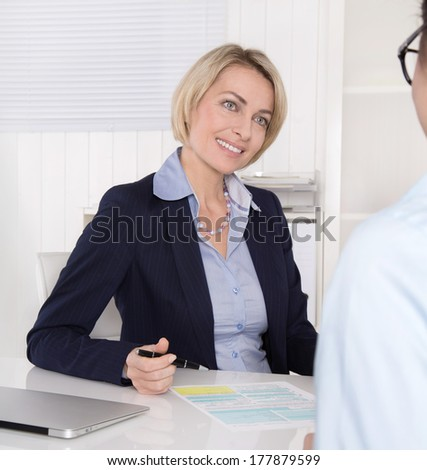 Interview with young female and mature manager at office.
