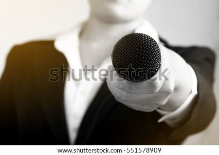 Interviewer making speech with microphone and hand gesturing concept for explaining interview, selective focus.