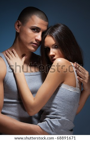 Intimacy moment of a couple hugging and hugging wearing grey clothes on dark background
