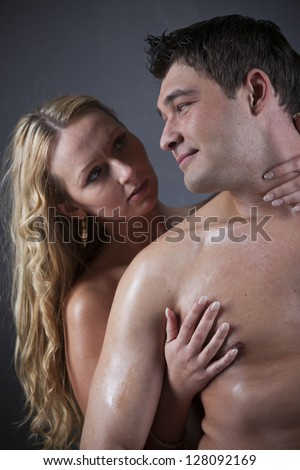 Intimacy - naked couple embracing over grey background