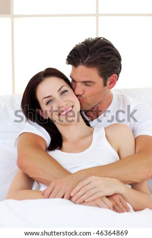 Intimate couple hugging lying in the bed - stock photo