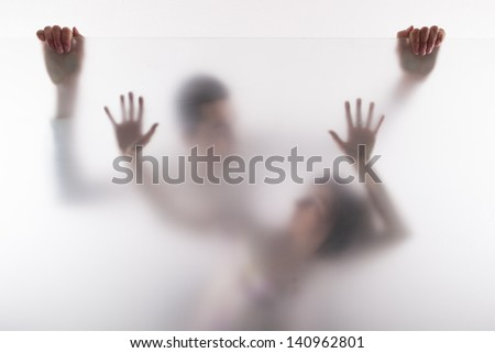 Intimate couple of man and woman posing behind the milk glass - stock photo