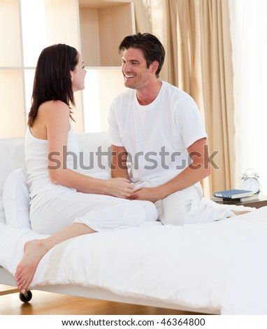 Intimate couple smiling sitting on the bed