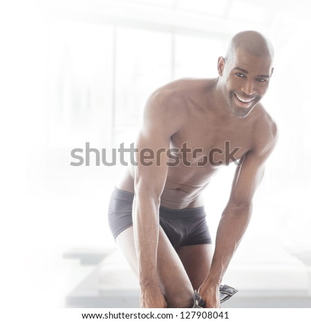 Intimate fun portrait of a young fit man putting his pants on with great smile