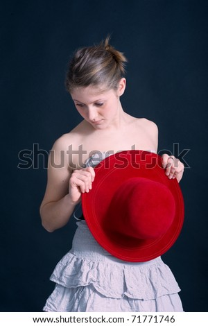 Intimate portrait of beautiful blonde caucasian girl with red hat. - stock photo