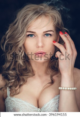 Intimate ring light studio portrait of sexy blonde woman smoking a rolled cigarette - stock photo