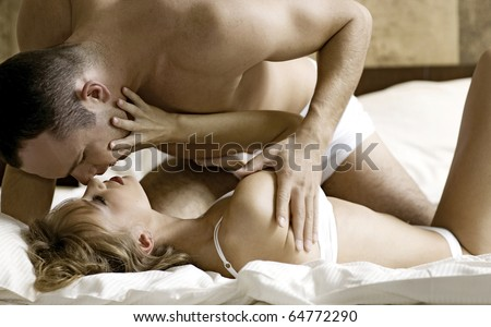 intimate young couple during foreplay in bed - stock photo