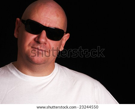 Intimidating looking security bouncer guy with shaved head wearing black sunglasses - stock photo