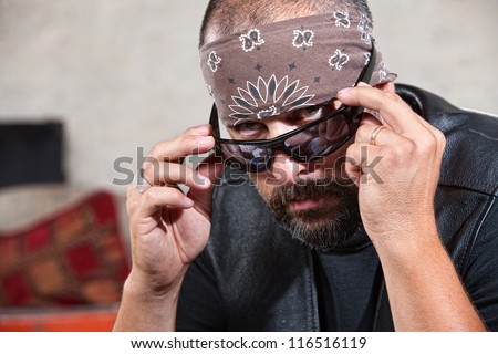 Intimidating male biker in bandanna looking over his sunglasses