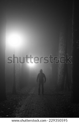 Intimidating man standing in a lane on a foggy night. Black and white. - stock photo
