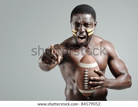Intimidating portraits of a black american football sportsman in studio - stock photo