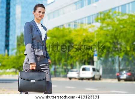 Into the ultra-modern business trends. Business woman with briefcase in modern office district looking into the distance - stock photo