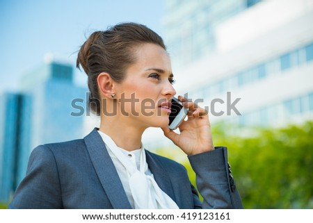 Into the ultra-modern business trends. Portrait of confident business woman in modern office district talking smartphone - stock photo