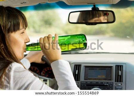Intoxicated woman drinking and driving as she swigs alcohol from the bottle while driving down the road - stock photo