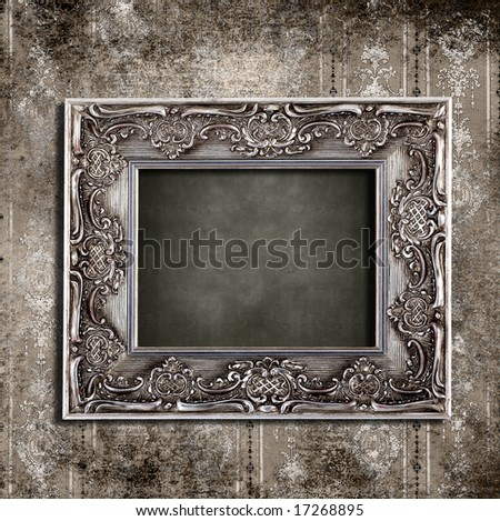Intricate old frame hanging on grungy vintage wallpaper - stock photo