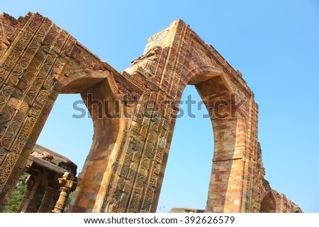 Intricate work of carvings and verses from holy Quran on the red and buff sandstone of Qutab Minar entrance arch - stock photo