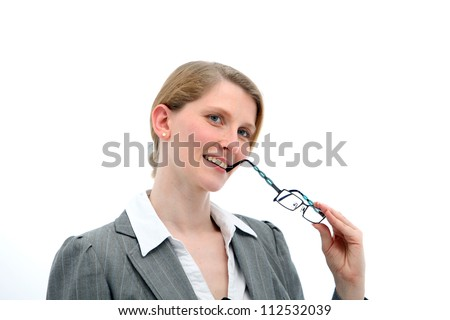 Introspective woman thinking and watching with her head tilted to one side and her glasses to her mouth