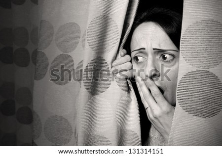intruder, woman hiding behind curtains black and white - stock photo