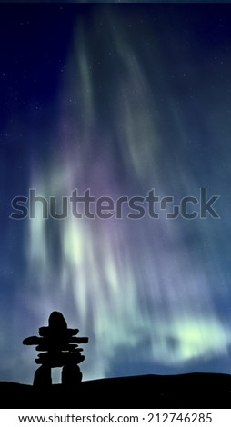 Inukshuk and Northern Lights Saskatchewan Canada colorful - stock photo