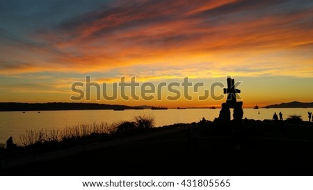 Inukshuk at English Bay Beach overlooking the Vancouver Harbor entrance - stock photo