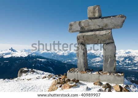 Inukshuk at the top of Whistler Mountain, site of 2010 Winter Olympics, with the Black Tusk peak in the background mountain range; in British Columbia, Canada