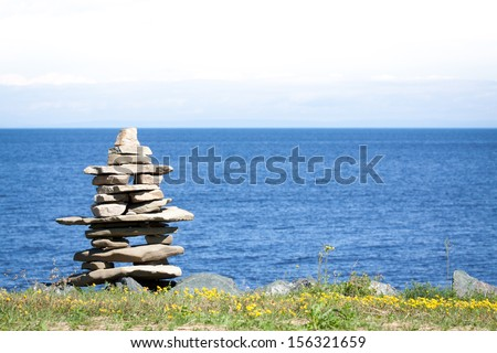 Inukshuk in front of the blue ocean, Canada. Inukshuk was used in  traditional caribou hunting by the indians.