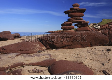 Inukshuk made of Red rocks on a Prince Edward Island Beach Canada - stock photo