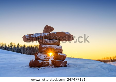 Inukshuk with dusting of snow at sunset - stock photo