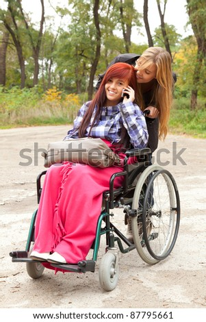 invalid girl on the wheelchair with mobie phone and friend outdoors - stock photo