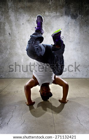 Inverted black breakdancer doing a headstand or handstand or urban yoga - stock photo