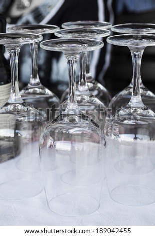 Inverted empty wine glasses on the table, toning - stock photo