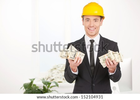 Invesments. Happy young man in formalwear and hardhat holding money and smiling - stock photo